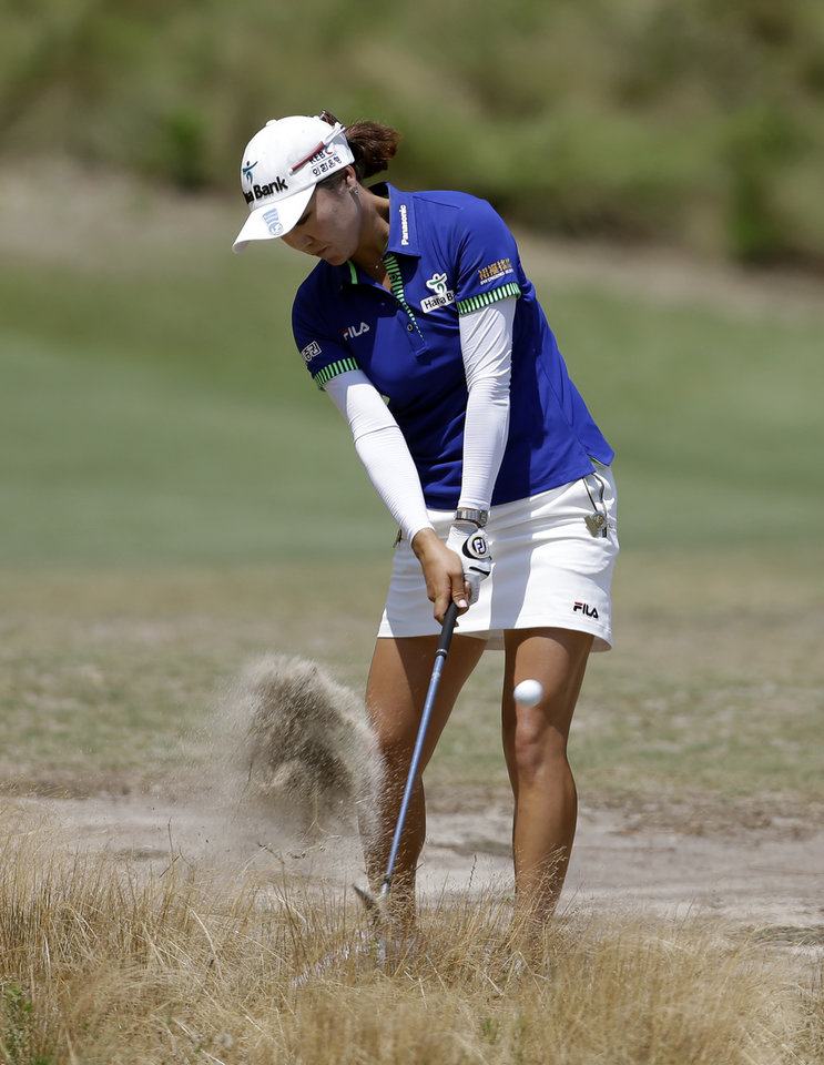 Photo - So Yeon Ryu, of South Korea, hits from a waste area on the 12th hole during the first round of the U.S. Women's Open golf tournament in Pinehurst, N.C., Thursday, June 19, 2014. (AP Photo/Bob Leverone)