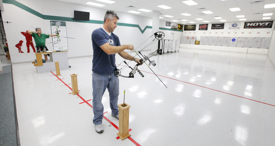 Photo - Justin Gerads, Yukon, shooting a bow at the 20 yard archery range inside H & H Shooting Sports, 400 S Vermont, in Oklahoma City Wednesday, June 25, 2014.  Photo by Paul B. Southerland, The Oklahoman