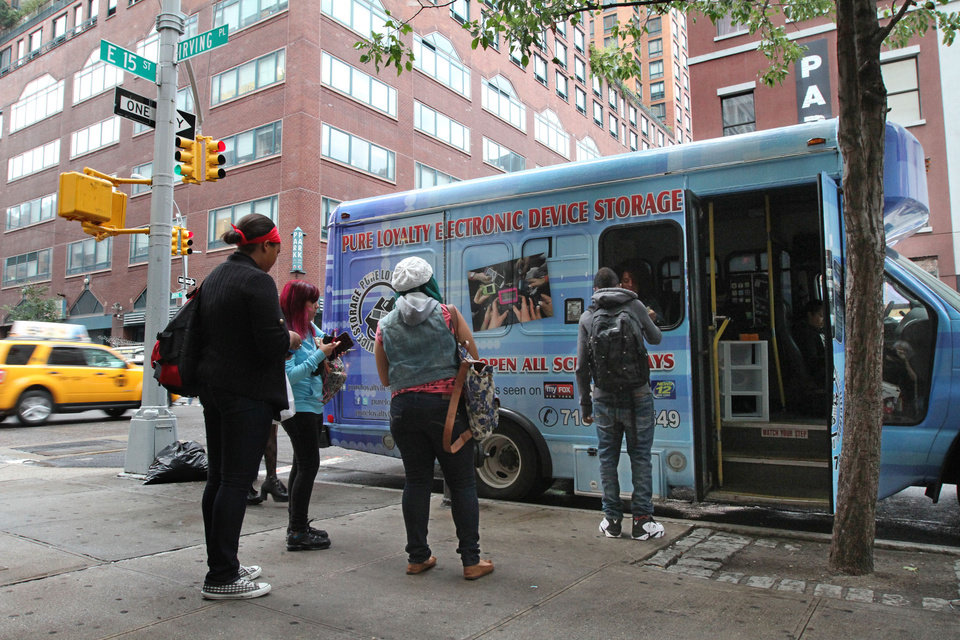 In this Sept. 27, 2012 photo, students from New York's Washington Irving educational complex line up to leave their cellphones and other electronic devices, for a dollar a day per item, in a privately operated truck parked near their school. Cellphones are banned in all New York City public schools, but the rule is widely ignored except in schools with metal detectors. Outside those schools, entrepreneurs park trucks where students drop off devices before class and get them back at the end of the day.(AP Photo/Tina Fineberg)