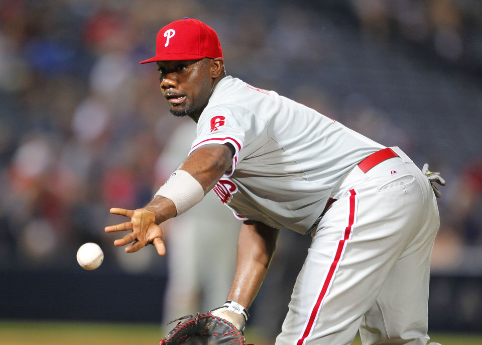 Photo - Philadelphia Phillies first baseman Ryan Howard (6) tosses to relief pitcher Jonathan Papelbon (58) for the out of Atlanta Braves Tommy La Stella in the ninth inning of a baseball game Tuesday, June 17, 2014, in Atlanta. (AP Photo/Todd Kirkland)