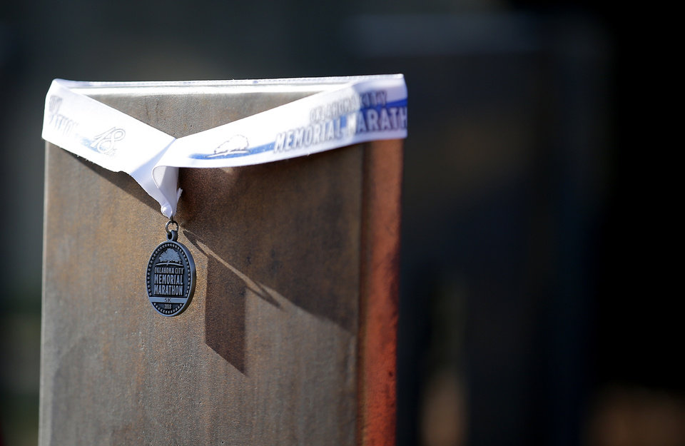 Photo - A medal is wrapped around a memorial chair following the Oklahoma City Marathon in Oklahoma City,  Sunday, April 29, 2018. Photo by Sarah Phipps, The Oklahoman