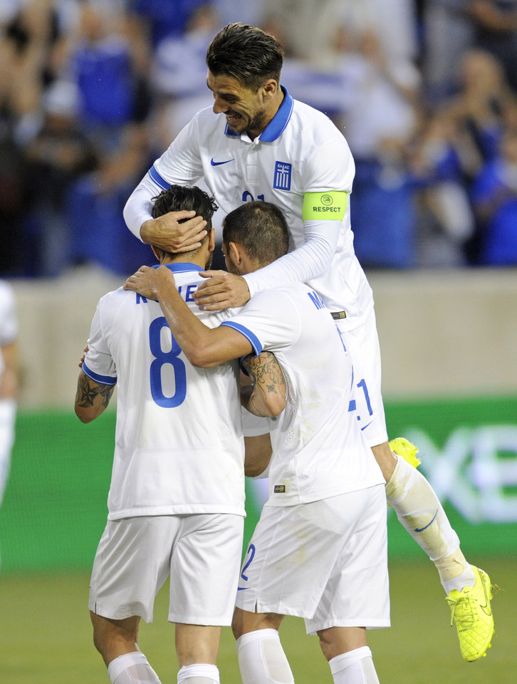 Photo - Greece's Kostantinos Katsouranis, top, and Ioannis Maniatis, right, celebrate with Guergki Panagiotis Kone (8) after Kone scored during the first half of an international friendly soccer match against Bolivia Friday, June 6, 2014, in Harrison, N.J.. (AP Photo/Bill Kostroun)