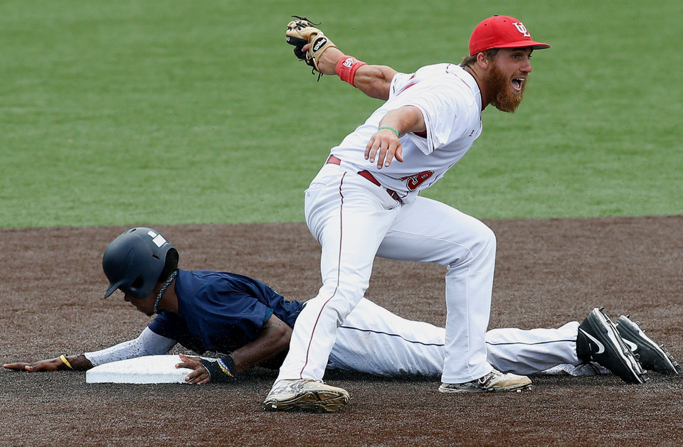 Photo - Jackson State's Gary Thomas, left, slides past Louisiana-Lafayette second baseman Jace Conrad, right, for a steal in the third inning during an NCAA college baseball tournament regional game, Sunday, June 1, 2014, in Lafayette, La. Louisiana-Lafayette won 11-1.  (AP Photo/Jonathan Bachman)