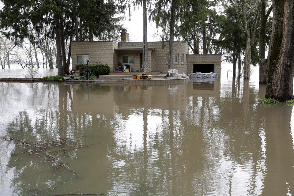 A home is surrounded by water Wednesday, April 24, 2013, in Peoria Heights, Ill. The Illinois River finally crested Tuesday at 29.35 feet, eclipsing a 70-year record in Peoria. (AP Photo/Seth Perlman)