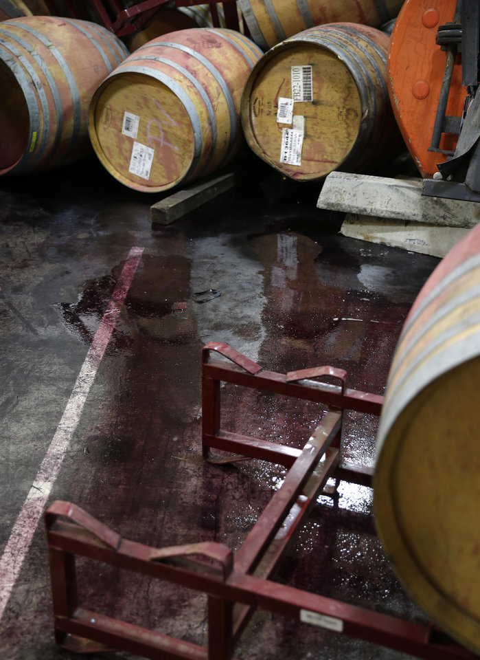 Photo - Wine leaks from some of the hundreds of earthquake damaged wine barrels at the Kieu Hoang Winery Monday, Aug. 25, 2014, in Napa, Calif. Winemakers in California's storied Napa Valley woke up Sunday to thousands of broken bottles, barrels and gallons of ruined wine as a result of Sunday's earthquake. (AP Photo/Eric Risberg)