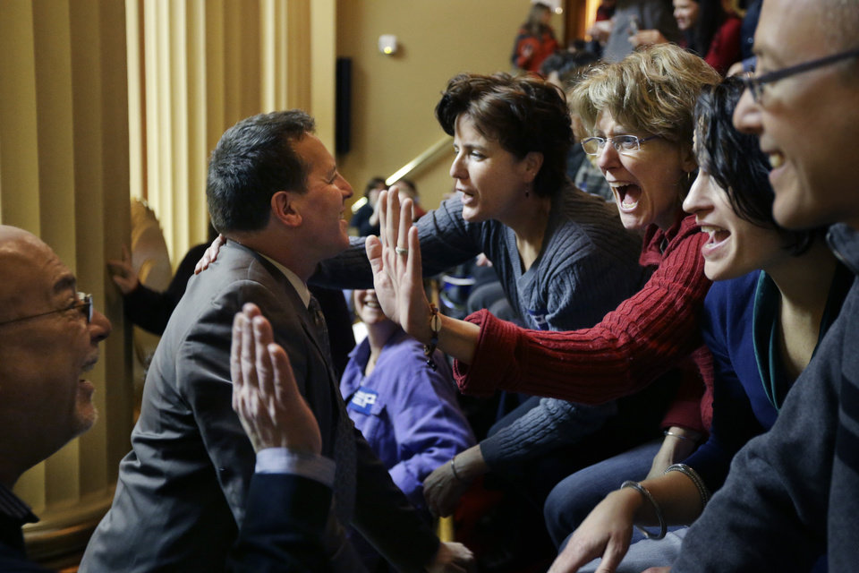 Rhode Island State Rep. Frank Ferri, D-Warwick, center left, and his partner Tony Caparco, far left, greet Wendy Baker, center right, and her partner Judy McDonnell, third from right, both of Providence, R.I., in the gallery of the House Chamber at the Statehouse, in Providence, Thursday, Jan. 24, 2013. Legislation to allow gay marriage in the state is headed for a vote Thursday in the House after being unanimously endorsed Tuesday by a legislative committee. (AP Photo/Steven Senne)