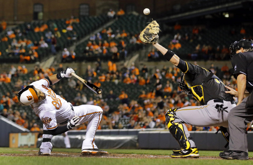 Photo - Baltimore Orioles' Manny Machado, left, ducks as Pittsburgh Pirates catcher Tony Sanchez, second from right, tries to catch a wide pitch in the fourth inning in the second baseball game of a doubleheader on Thursday, May 1, 2014, in Baltimore. (AP Photo/Patrick Semansky)