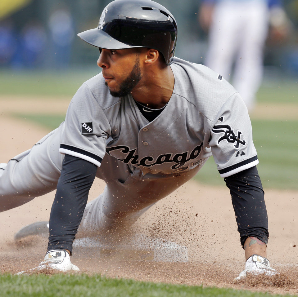 Photo - Chicago White Sox second baseman Leury Garcia slides into third base as the ball get past Kansas City Royals third baseman Danny Valencia during the ninth inning of a baseball game against the Kansas City Royals at Kauffman Stadium in Kansas City, Mo., Sunday, April 6, 2014. Garcia stole third base and scored on the overthrow. The White Sox won 5-1. (AP Photo/Orlin Wagner)