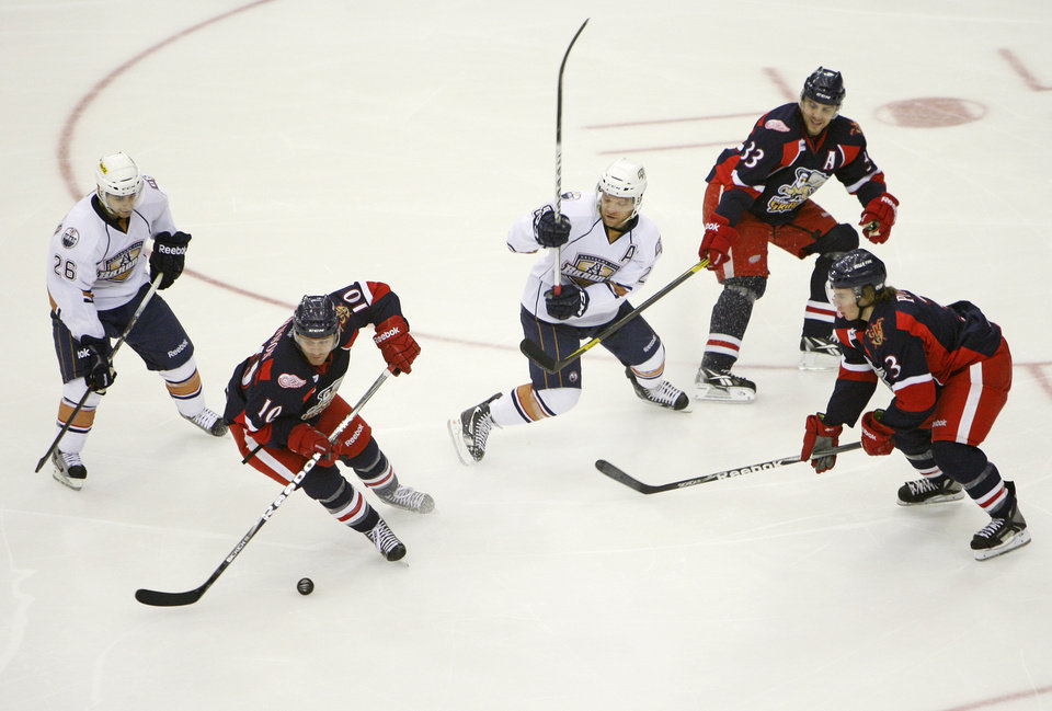 Photo - Grand Rapids' Jamie Johnson (10) skates away from Oklahoma City's Mark Arcobello (26) and Ryan Keller (28) near teammates Doug Janik (33) and Logan Pyett (3) during an AHL hockey game between the Oklahoma City Barons and the Grand Rapids Griffins at the Cox Convention Center in Oklahoma City, Saturday, March 24, 2012. Photo by Nate Billings, The Oklahoman