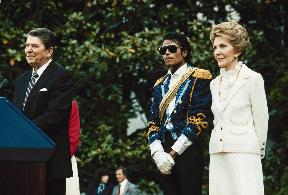 Photo - FILE - In this May 14, 1984, file photo, Michael Jackson , center, stands with President Ronald Reagan, left, and first lady Nancy Reagan  on the south lawn of the White House prior to receiving an award from the president for his contribution to the drunk driving awareness program. (AP Photo/Scott Stewart, file) ORG XMIT: NYET706
