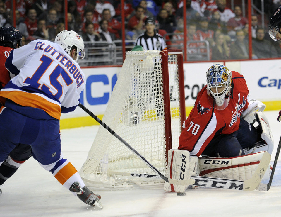 Photo - Washington Capitals goalie Braden Holtby (70) reaches for the puck against New York Islanders right wing Cal Clutterbuck (15) during the first period an NHL hockey game, Tuesday, Nov. 5, 2013, in Washington. (AP Photo/Nick Wass)