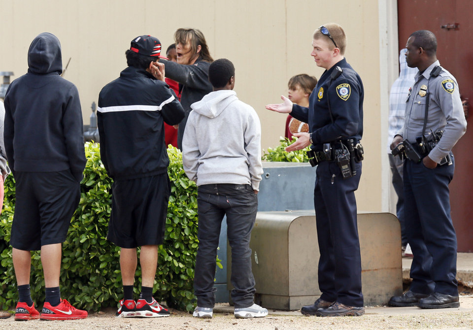 Photo - Oklahoma City police officers talk with residents while responding to a call Thursday at Willow Cliff Apartments.