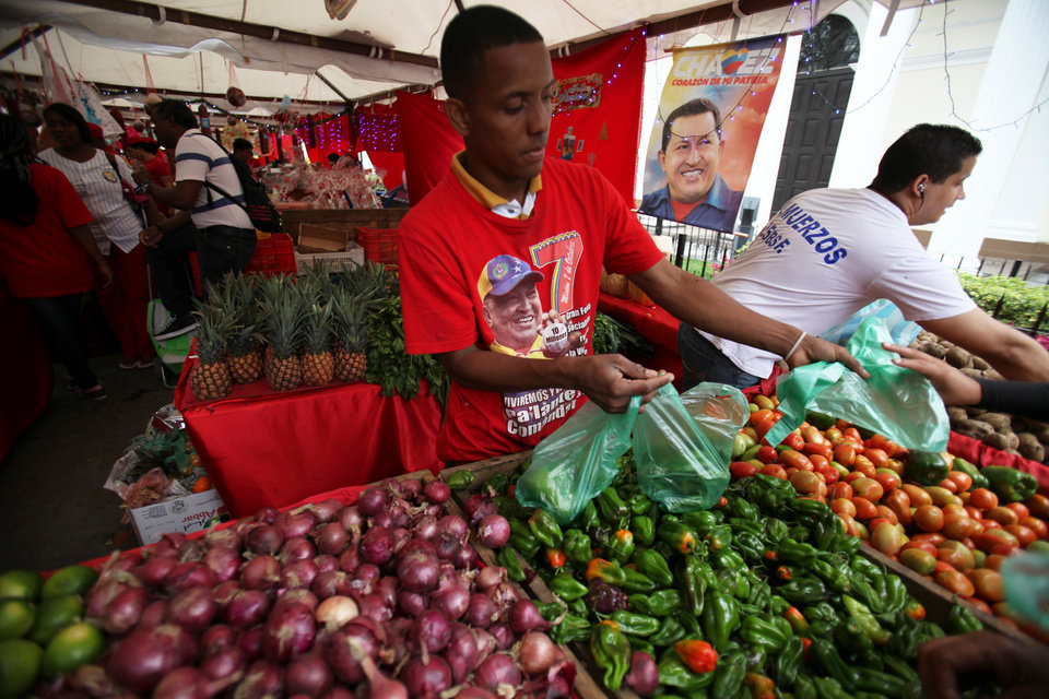A vendor wearing a T-shirt with an image of Venezuela's President Hugo Chavez sells vegetable at a state-run market in Caracas, Venezuela, Friday, Dec. 28, 2012. The obsessive, circular conversations about Chavez's health dominate family dinners, plaza chit-chats and social media sites in this country on edge since its larger-than-life leader went to Cuba for emergency cancer surgery more than two weeks ago. The man whose booming voice once dominated the airwaves for hours at a time has not been seen or heard from since.(AP Photo/Fernando Llano)