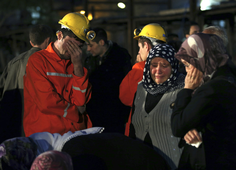 Photo - Miners and family members wait outside a coal mine following an explosion in Soma, western Turkey, early Wednesday, May 14, 2014. Rescuers desperately raced against time to reach more than 200 miners trapped underground Wednesday after an explosion and fire at the coal mine in western Turkey killed over 200 workers, authorities said, in one of the worst mining disasters in Turkish history. (AP Photo/Emrah Gurel)