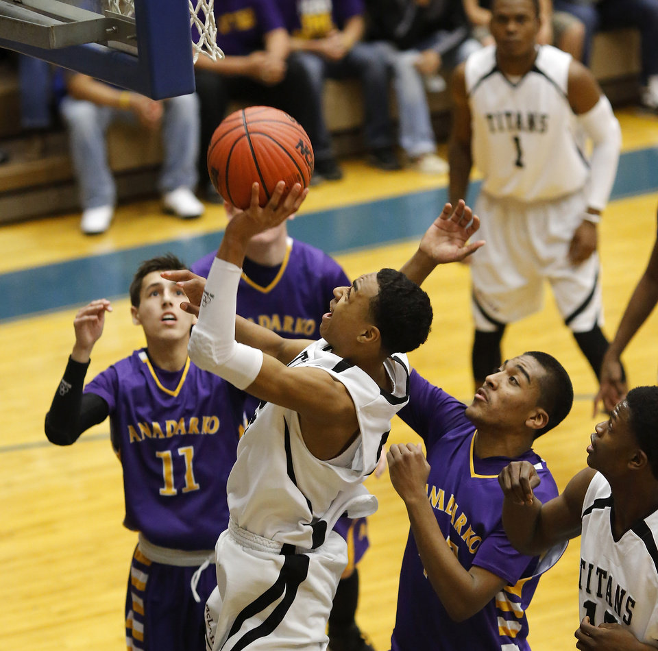 Photo - Tulsa McLain's Nick Foster is surrounded by Anadarko players Silas Lambert, left, and A'Ram Johnson as he gathers in his own rebound and goes up for another basket attempt during first round games of Class 4A basketball state tournament in the Lyle Boren Activity Center at Choctaw High School on Thursday,  March 7, 2013.  McLain won 40-38.  Photo by Jim Beckel, The Oklahoman