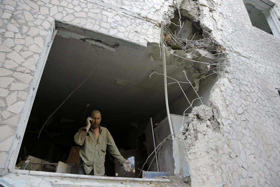 Photo - Valery who gave only his first name calls in a room of his damaged house after shelling in the city of Slovyansk, Donetsk Region, eastern Ukraine Monday, June 30, 2014. Residential areas came under shelling on Monday morning from government forces. (AP Photo/Dmitry Lovetsky)