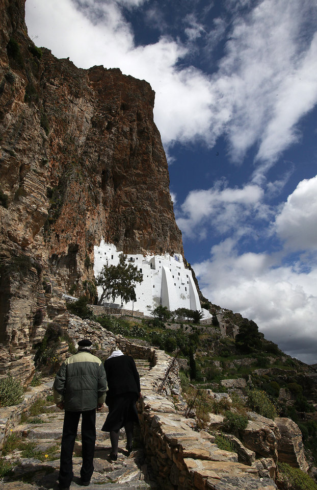 Photo - The faithful procede uphill to the 8th century Greek Orthodox monastery of Virgin Mary Hozoviotissa, to participate to the Good Friday procession, in the Greek island of Amorgos on Friday April 18, 2014. More than 250 million Orthodox Christians worldwide will celebrate Easter this year on Sunday, April 20. (AP Photo/Dimitri Messinis)