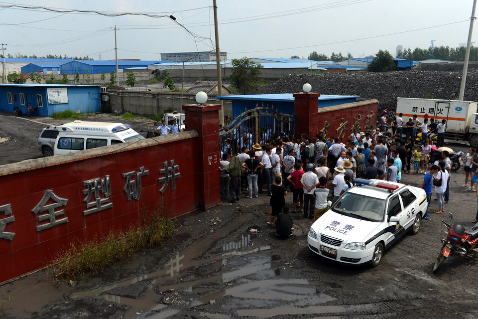 Photo - In this Aug. 19, 2014 photo,  people gather outside the Dongfang Coal Mine in Huainan city, east China's Anhui Province. An explosion Tuesday in the coal mine in eastern China trapped 27 workers underground, state media reported. (AP Photo/Xinhua, Zhang Duan) NO SALES