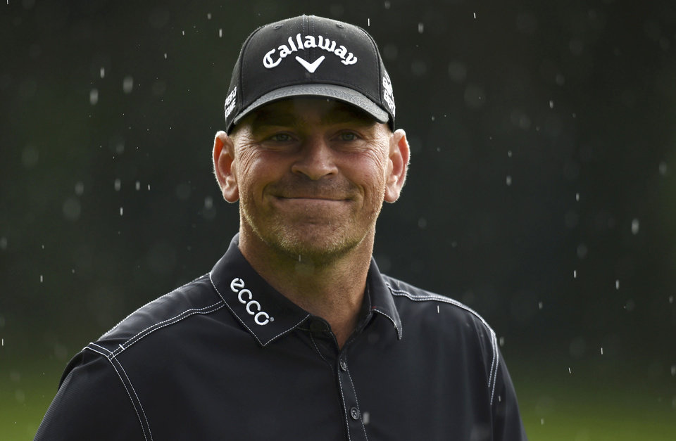 Photo - Denmark's Thomas Bjorn  smiles in the rain on the 18 green during day one of the  BMW PGA Championship at the Wentworth Club,  Virginia Water England Thursday May 22, 2014. Bjorn shot a 10-under-par 62 in the first round.(AP PhotoAdam Davy/PA) UNITED KINGDOM OUT