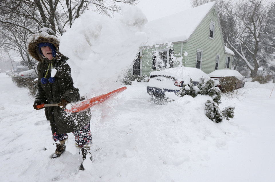 Photo - Peggy Udden, of Norwood, Mass., shovels her driveway in Norwood, Wednesday, Feb. 5, 2014. Six to 12 inches of snow is expected around Boston, with 3 to 6 inches in southeastern areas before changing to sleet and rain Wednesday. (AP Photo/Steven Senne)