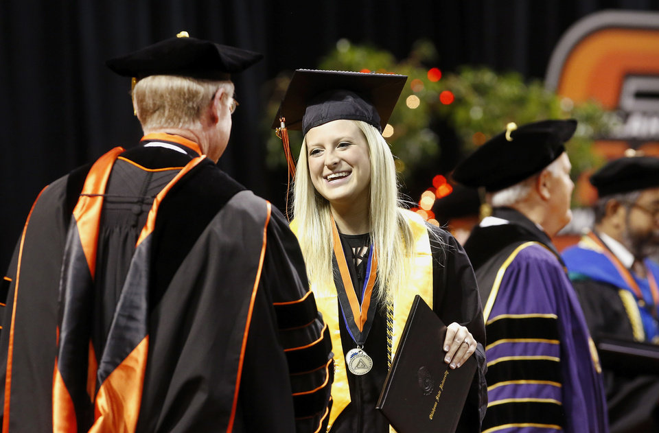 OSU President Burns Hargis, left, and platform guests greet each graduate as they walk across the stage. Undergraduates at OSU participated in the school's 127th commencement ceremony the weekend of Friday, May 3 and Saturday, May 4, 2013 inside Gallagher-Iba Arena on the university's campus.These photos were taken at the Saturday morning ceremony when students from the College of Agricultural Sciences and Natural Resources, and the Spears School of Business were conferred with degrees.   Photo  by Jim Beckel, The Oklahoman.