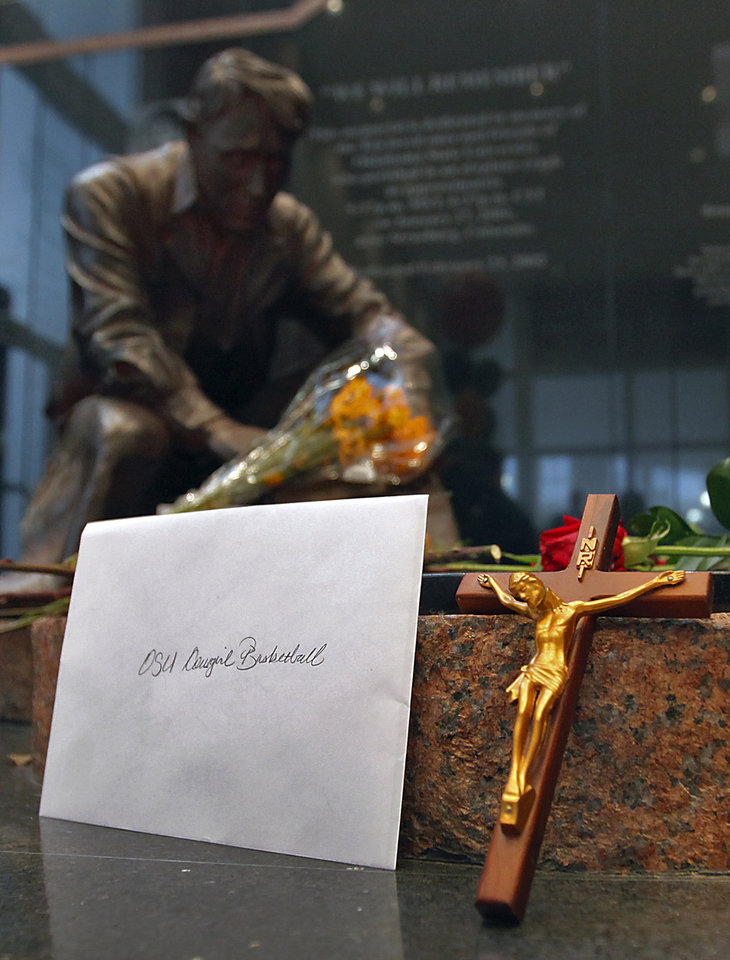 Photo - Memorial items are left around the Remember the 10 statue plane crash memorial during the memorial service for Oklahoma State head basketball coach Kurt Budke and assistant coach Miranda Serna at Gallagher-Iba Arena on Monday, Nov. 21, 2011 in Stillwater, Okla. The two were killed in a plane crash along with former state senator Olin Branstetter and his wife Paula while on a recruiting trip in central Arkansas last Thursday. Photo by Chris Landsberger, The Oklahoman