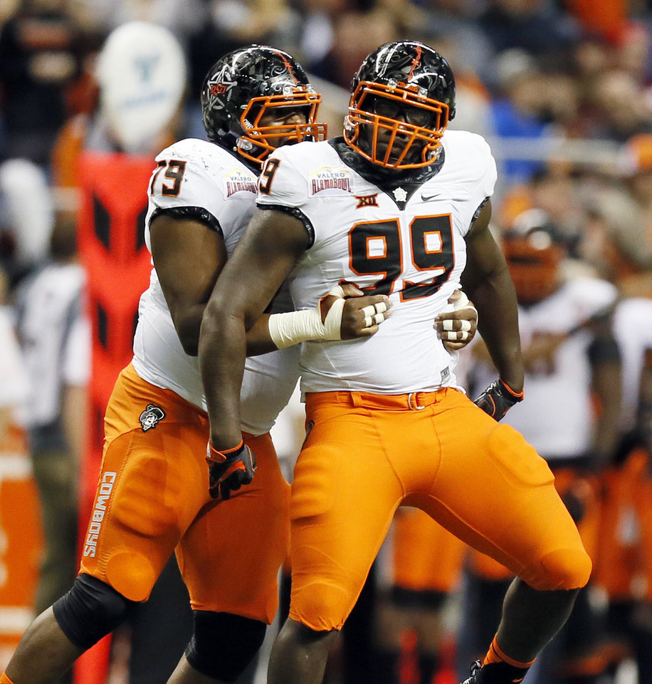 Photo -  Oklahoma State's Darrion Daniels, left, and Trey Carter celebrate a sack by Carter during the Cowboys' Alamo Bowl victory over Colorado. PHOTO BY NATE BILLINGS, The Oklahoman