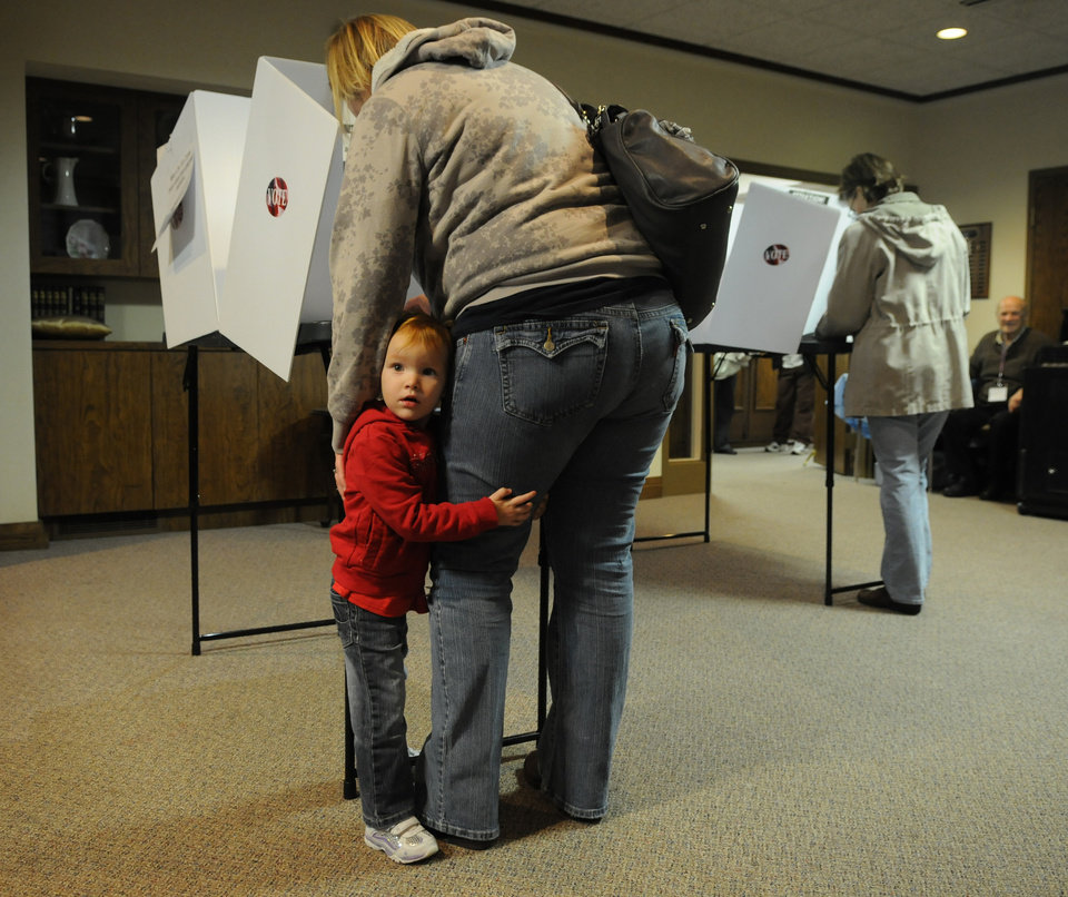 Photo -   Alexis Svetlick, 2, of Moline Ill., sticks close to her mother, Jennifer Svetlick, while she votes at First Christian Church in Moline, Ill. on Tuesday Nov. 6, 2012. Morning rain did not deter voters from heading to the polls, with long lines reported at numerous polling places. (AP Photo/The Dispatch, Todd Mizener) QUAD CITY TIMES OUT