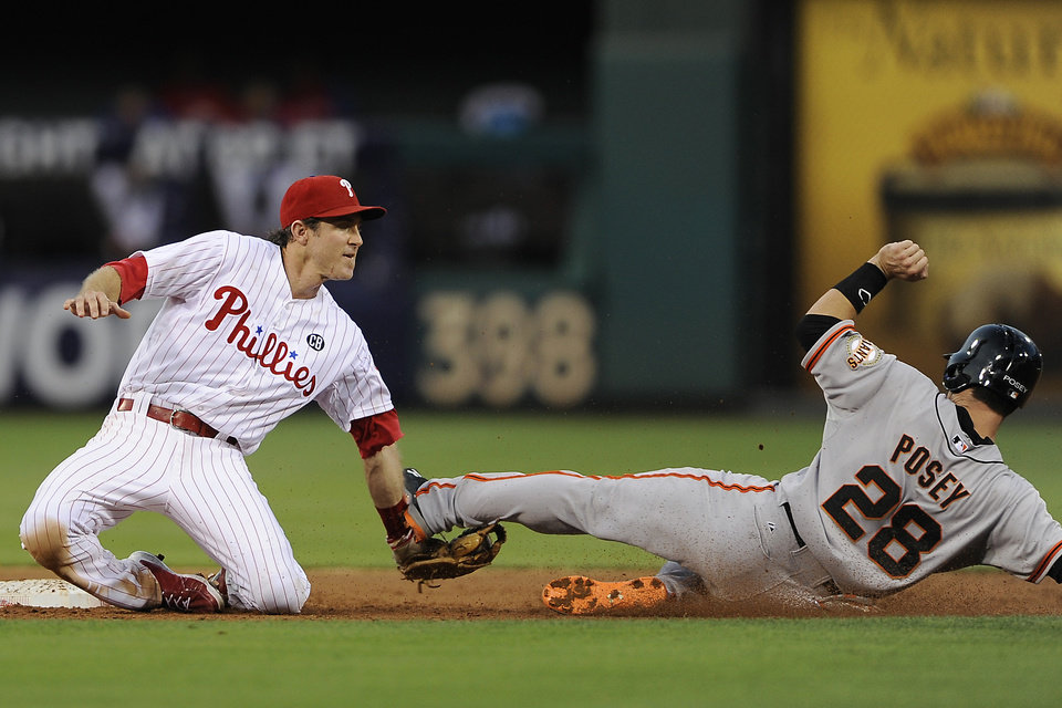 Photo - Philadelphia Phillies second baseman Chase Utley, left, tags San Francisco Giants' Buster Posey for the final out in the second inning inning of a baseball game on Monday, July 21, 2014, in Philadelphia. (AP Photo/Michael Perez)