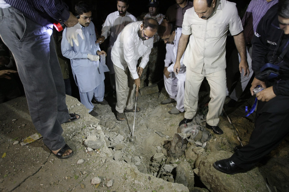 Photo - Pakistani investigators examine the site of bombing in Karachi, Pakistan, Thursday, Aug. 22, 2013. A roadside bomb hit a convoy of security forces in the southern city of Karachi on Thursday night, killing one person and wounding 20 others, said police official Ishtiaq Ahmed. No one has claimed responsibility for the attack, but suspicion likely will fall on the Taliban. (AP Photo/Fareed Khan)