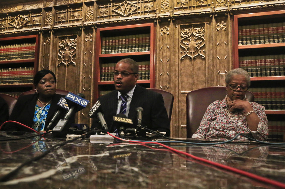 Photo - Attorney Derek Sells, center, sets between between Alma Murdough, right, and Cheryl Warner, left, the mother and sister of former Marine Jerome Murdough, during a news conference on Friday May 16, 2014 in New York.  Sells plans to file a wrongful death lawsuit against the city on behalf of Alma Murdough for the death of her son, who was found dead in a 100 degree cell on Rikers Island.  (AP Photo/Bebeto Matthews)
