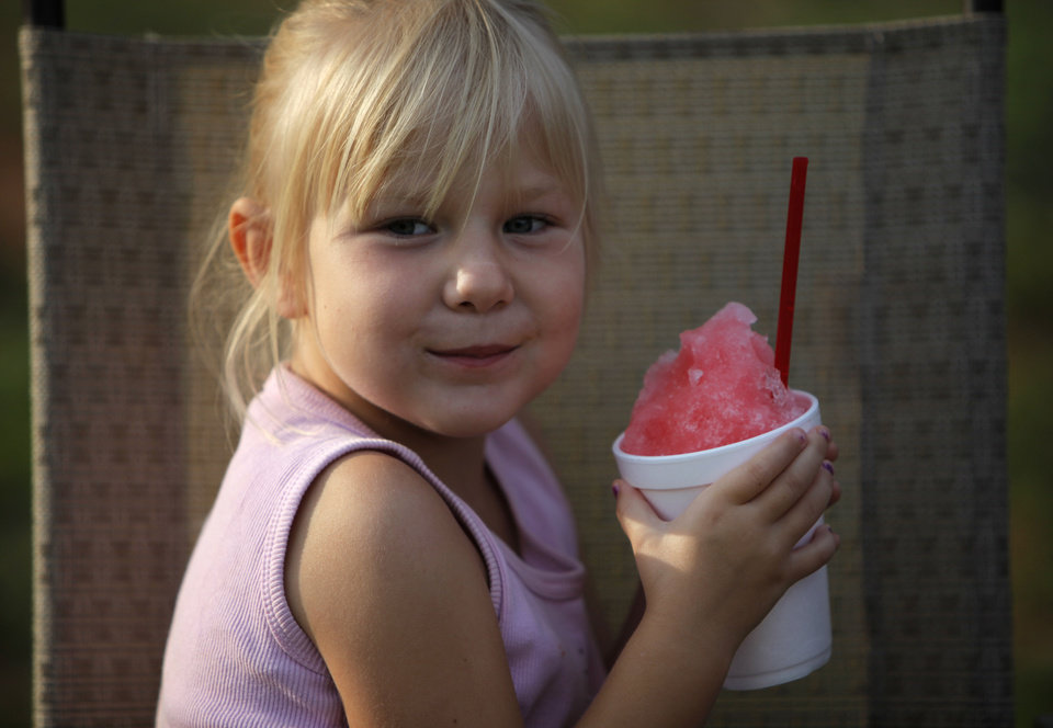 Photo - Arryana Clark, 5, of Midwest City, enjoys a snow cone during the Midwest Twilight Concert in Midwest City on Thursday.  Garett Fisbeck - THE OKLAHOMAN
