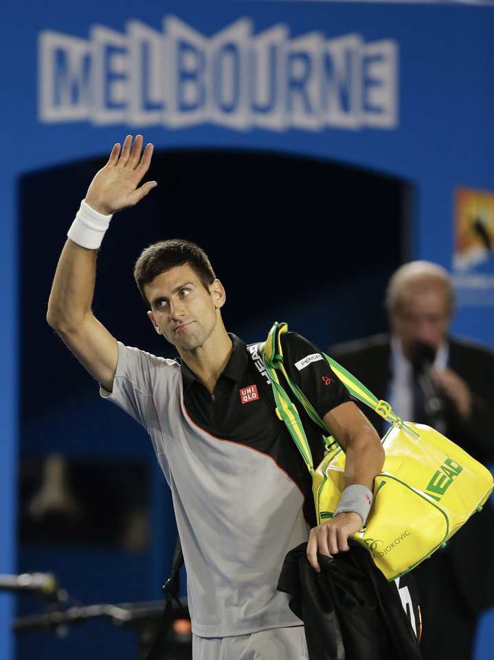Photo - Novak Djokovic of Serbia waves to the crowd after losing his quarterfinal match against Stanislas Wawrinka of Switzerland at the Australian Open tennis championship in Melbourne, Australia, Tuesday, Jan. 21, 2014.(AP Photo/Rick Rycroft)