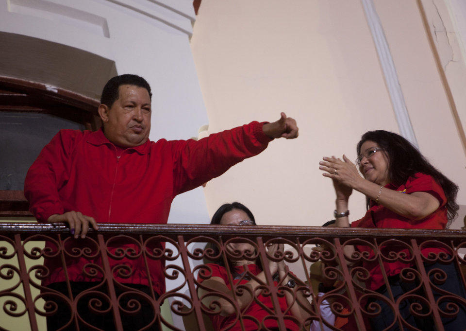 Venezuela\'s President Hugo Chavez greets his supporters from the Miraflores presidential palace balcony in Caracas, Venezuela, Sunday, Oct. 7, 2012. Chavez won re-election and a new endorsement of his socialist project Sunday, surviving his closest race yet after a bitter campaign against opposition candidate Henrique Capriles.(AP Photo/Rodrigo Abd)