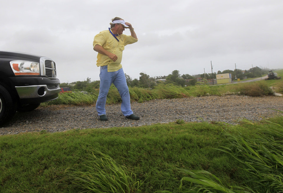 Photo - P.J. Hahn, Coastal Zone Director for Plaquemnies Parish, walks on a levee to survey flooding from Isaac, which is expected to make landfall in the region as a hurricane this evening in Venice, La.,  the southernmost tip of the state, Tuesday, Aug. 28, 2012.  Forecasters at the National Hurricane Center warned that Isaac, especially if it strikes at high tide, could cause storm surges of up to 12 feet (3.6 meters) along the coasts of southeast Louisiana and Mississippi and up to 6 feet (1.8 meters) as far away as the Florida Panhandle. (AP Photo/Gerald Herbert) ORG XMIT: LAGH115