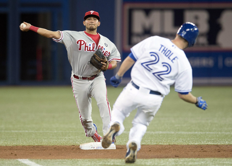 Photo - Philadelphia Phillies' Freddy Galvis, left, turns a double play over Toronto Blue Jays' Josh Thole during the second inning of a baseball game in Toronto on Thursday, May 8, 2014. The Blue Jays' Chris Getz grounded into double play. (AP Photo/The Canadian Press, Darren Calabrese)