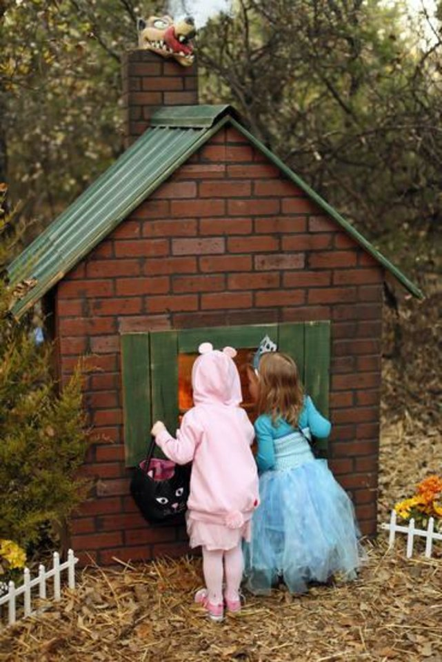 Photo -  Allison Miller, 2, left, and Sage Son, 2, peek inside a house from