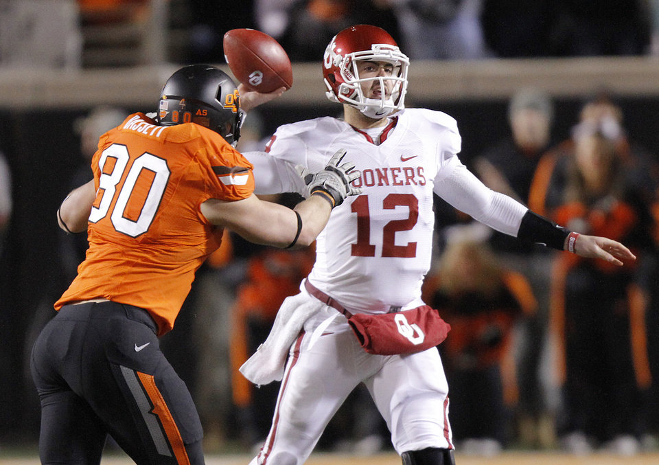 Oklahoma State\'s Cooper Bassett (80) puts pressure on Oklahoma\'s Landry Jones (12) during the Bedlam college football game between the Oklahoma State University Cowboys (OSU) and the University of Oklahoma Sooners (OU) at Boone Pickens Stadium in Stillwater, Okla., Saturday, Dec. 3, 2011. Photo by Chris Landsberger, The Oklahoman