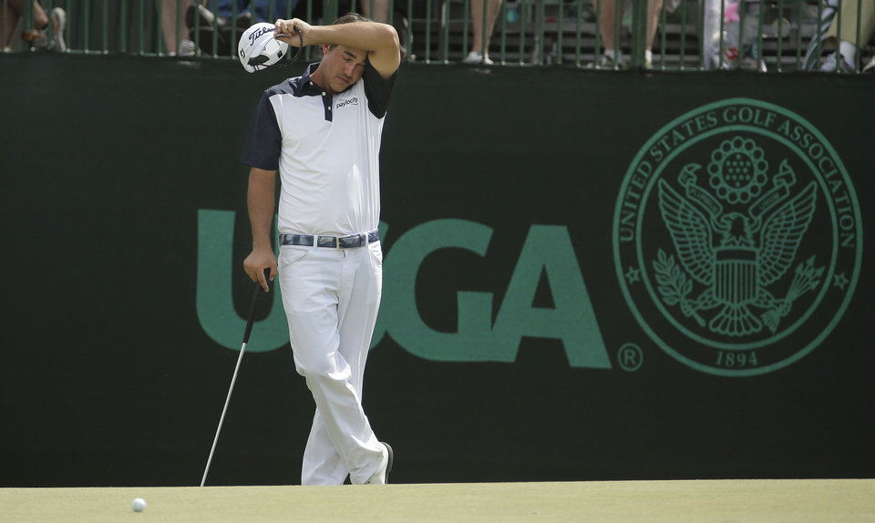Photo - Brooks Koepka wipes his face on the the 11th green during the first round of the U.S. Open golf tournament in Pinehurst, N.C., Thursday, June 12, 2014. (AP Photo/Charlie Riedel)