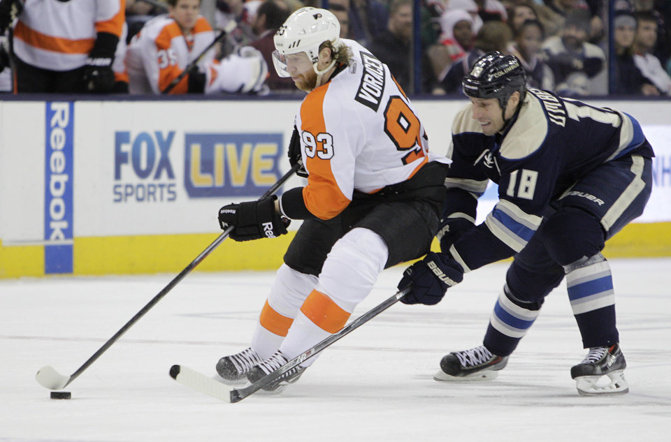 Photo - Philadelphia Flyers' Jakub Voracek, left, of the Czech Republic, carries the puck across the blue line as Columbus Blue Jackets' RJ Umberger defends during the third period of an NHL hockey game Thursday, Jan. 23, 2014, in Columbus, Ohio. The Blue Jackets beat the Flyers 5-2. (AP Photo/Jay LaPrete)