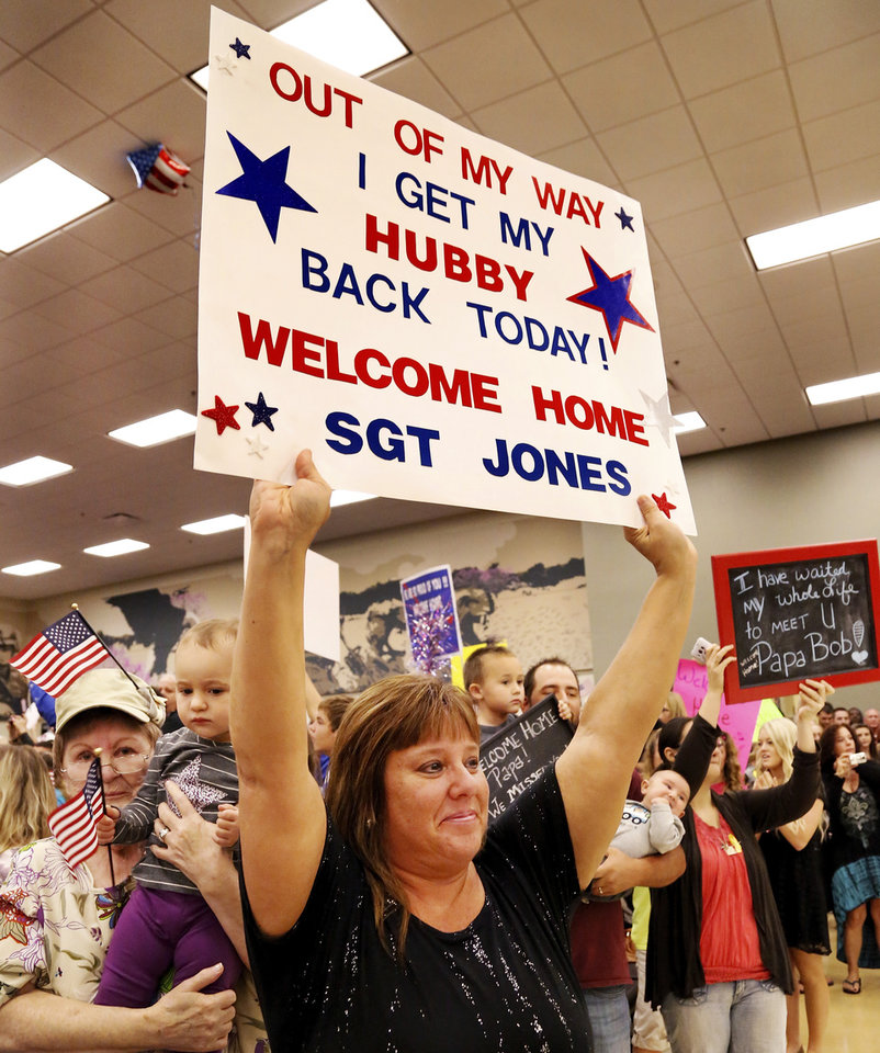 Photo - Jennifer Jones holds a sign she made to welcome her husband, Sgt. Robert Jones, back home. Behind her are other family members who came with her to welcome Sgt. Jones home from an extended deployment overseas. At least 1,000 people, mostly spouses, children, relatives and friends, crowded into a large room in the Armed Forces Reserve Center in Norman on Saturday, Sep. 28, 2013, to give a boisterous, and at times, tearful welcome  to members of the Oklahoma National Guard who returned to Norman after 10 months in Afghanistan. After a brief ceremony, which included a personal thank-you to his troops from Maj. Gen. Myles Deering, the soldiers were dismissed to an emotional reunion with their love ones. Deering serves as adjutant general of Oklahoma.  Photo  by Jim Beckel, The Oklahoman.