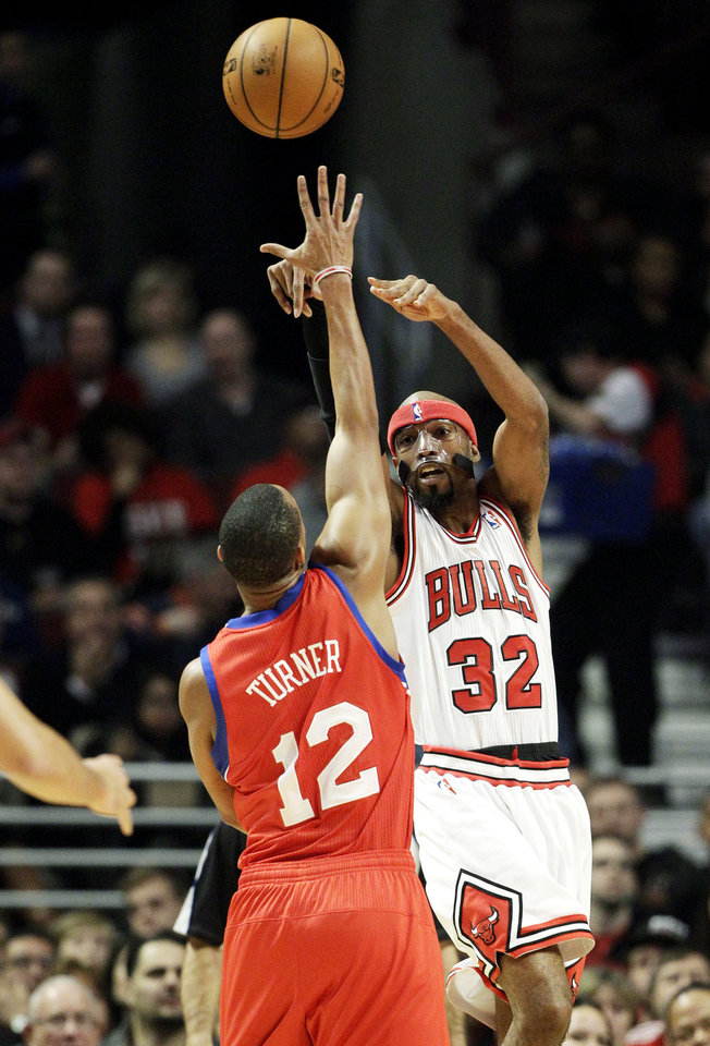 Chicago Bulls guard Richard Hamilton, right, passes over Philadelphia 76ers forward Thaddeus Young during the first half of an NBA basketball game in Chicago on Saturday, Dec. 1, 2012. (AP Photo/Nam Y. Huh)