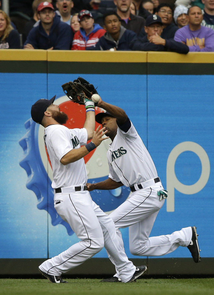 Photo - Seattle Mariners center fielder Austin Jackson, right, commits a fielding error as he collides with left fielder Dustin Ackley, left, as they fail to catch a ball hit by Denard Span in the first inning of a baseball game, Saturday, Aug. 30, 2014, in Seattle. (AP Photo/Ted S. Warren)