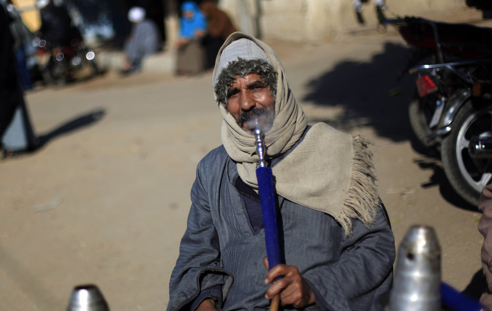 Photo - An Egyptian man smokes a water pipe outside a polling station as he waits to cast his vote during the second round of a referendum on a disputed constitution drafted by Islamist supporters of President Mohammed Morsi in Fayoum, about 100 kilometers (62 miles) south of Cairo, Egypt, Saturday, Dec. 22, 2012.(AP Photo/Khalil Hamra)