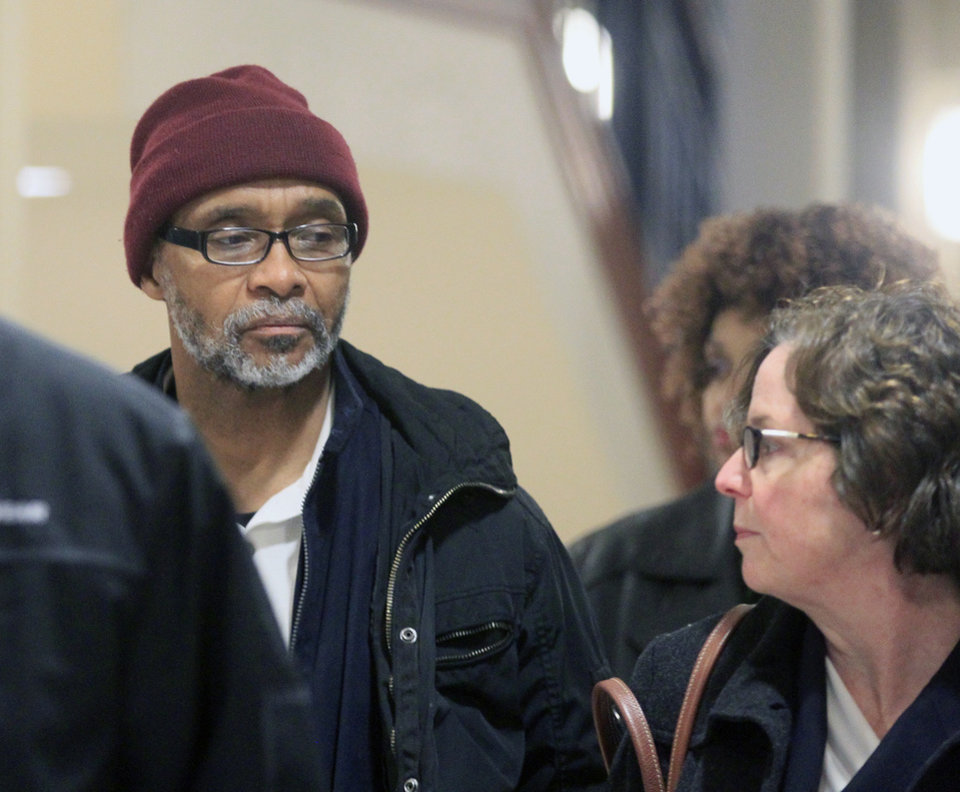 Photo - Douglas Prade arrives with his attorney Lisa Gates, right, and his sister Yvonne Prade for his hearing at the Summit County Courthouse, Thursday, March 20, 2014, in Akron, Ohio. A judge ordered Douglas Prade to appear in court Thursday so she could decide whether he should be sent back to prison or remain free while he appeals. He could head back to prison after being exonerated in his ex-wife's killing, he served 15 years. (AP Photo/Akron Beacon Journal, Karen Schiely)  MANDATORY CREDIT