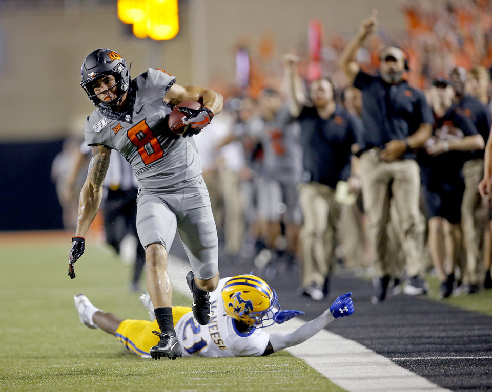 Photo - Oklahoma State's Braydon Johnson (8) gets by Andre Sam (21) as he runs in for a touchdown in the third quarter during the college football game between the Oklahoma State Cowboys and the McNeese State Cowboys at Boone Pickens Stadium in Stillwater, Okla., Saturday, Sept. 7, 2019. [Sarah Phipps/The Oklahoman]