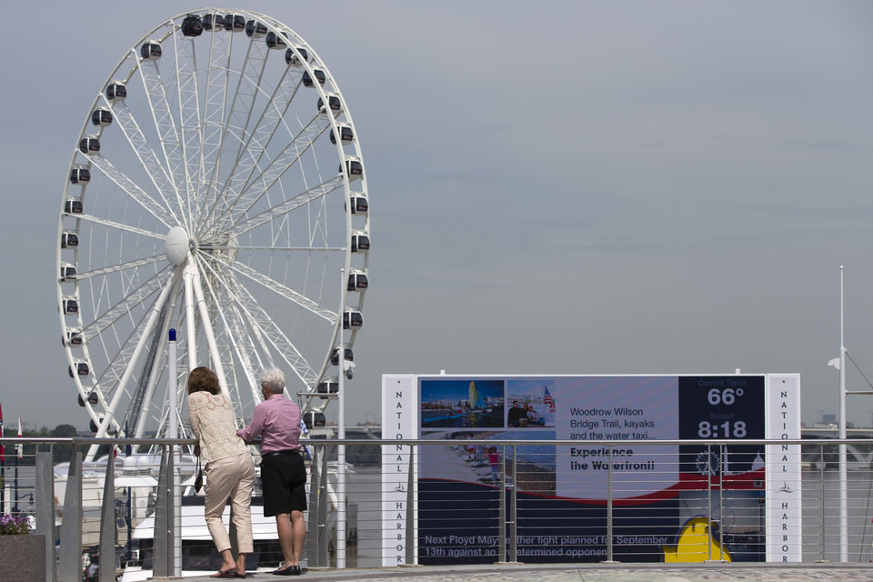 Photo - This photo taken May 20, 2014 shows a new Ferris wheel overlooking Washington at National Harbor in Oxon Hill, Md. With a massive new Ferris wheel overlooking the nation's capital, a children's museum, a village of restaurants and hotels and a major casino resort on the horizon, National Harbor in Maryland has quickly become a travel alternative to the marble monuments and museums of nearby Washington. (AP Photo/ Evan Vucci)