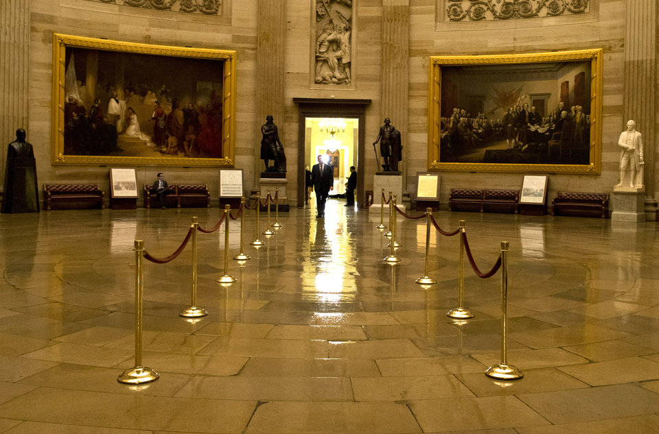 Photo - A man walks through a nearly empty Capitol Rotunda during the late hours of a continuing budget battle on Capitol Hill on Monday, Sept. 30, 2013 in Washington. The Republican-controlled House and the Democrat-controlled Senate are at an impasse as Congress continues to struggle over how to prevent a possible shutdown of the federal government when it runs out of money. (AP Photo/Evan Vucci)