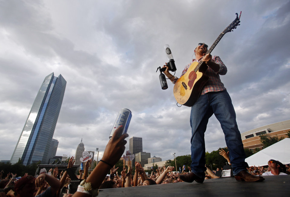Photo - Josh Abbott fires a t-shirt into the air from a air powered t-shirt gun during a break in his performance at OKC Fest in downtown Oklahoma City on Friday, June 27, 2014. OKC Fest is a new two day country music festival with multiple stages downtown. Photos by KT King/The Oklahoman