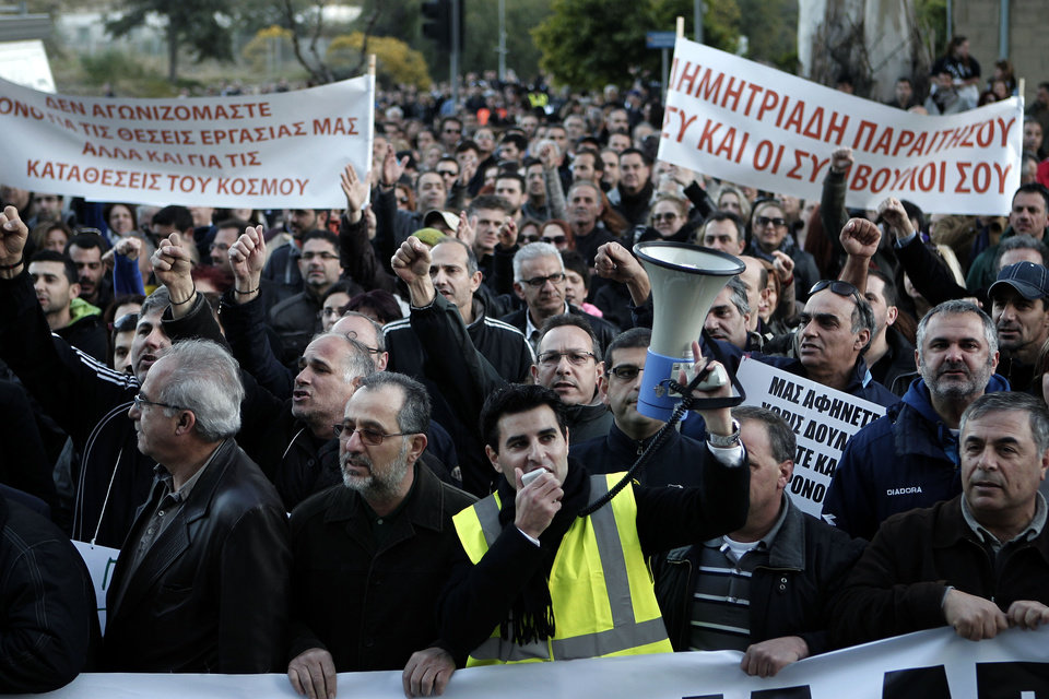 Photo - Bank employees protest outside the ministry of finance on Saturday, March 23, 2013. Thousands of bank employees took part in a protest that ended outside the Cypriot parliament. Politicians in Cyprus were racing Saturday to complete an alternative plan raising funds necessary for the country to qualify for an international bailout, with a potential bankruptcy just three days away. Banner at left reads: We fight not only for our jobs but also for people's savings